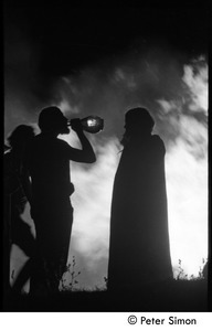 After the Maypole celebration, Packer Corners commune: silhouette and bonfire, with man drinking wine from a bottle