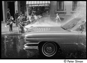 Children playing in the spray of an opened fire hydrant in front of Bayamon Grocery, Spanish Harlem