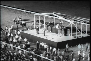 The Beatles performing at Suffolk Downs race track, police lined up in front of the stage