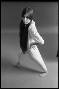 Full-length studio portrait of a model in a loose-fitting shift, hands on hips