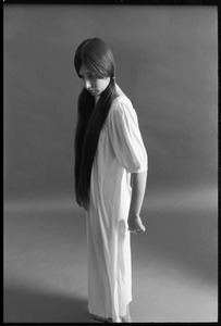 Full-length studio portrait of a model in a loose-fitting shift