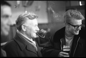 Man smoking a pipe and drinking with friends at the bar in a Scottish pub