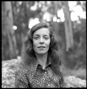 Woman posed on a granite boulder in a eucalyptus grove