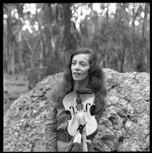 Woman posed with a fiddle, seated on a granite boulder in a eucalyptus grove