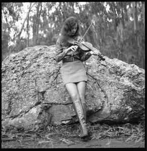 Woman playing a fiddle, posed on a granite boulder in a eucalyptus grove