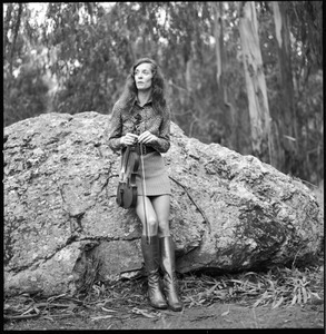Woman with a fiddle, posed on a granite boulder in a eucalyptus grove