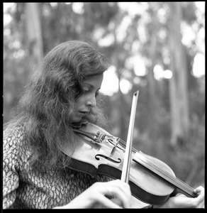 Close-up of woman playing a fiddle in a eucalyptus grove