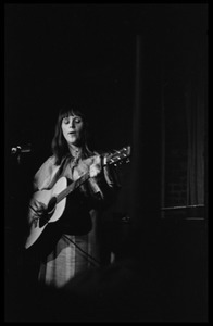 Woman acoustic guitarist performing on stage at the closing of Club 47