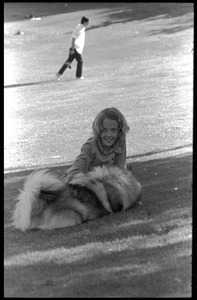 Young girl petting a dog on Cambridge Common