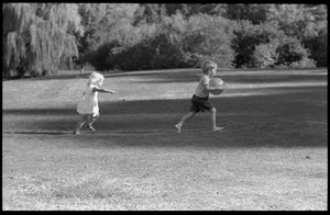 Children chasing around with a ball on Cambridge Common