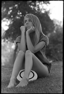 Young woman with Frisbee, sitting on the grass on Cambridge Common