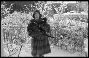 Woman in a heavy fur coat carrying her cat outside after a heavy snow