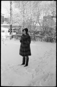 Woman in a heavy fur coat standing outside after a heavy snow