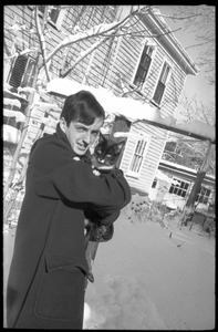 Charles Frizzell holding a tuxedo cat outside after a heavy snow