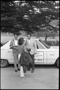 Visitors standing next to a courtesy car at Newport Jazz Festival