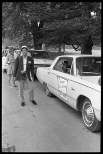 Visitor standing next to a courtesy car at Newport Jazz Festival