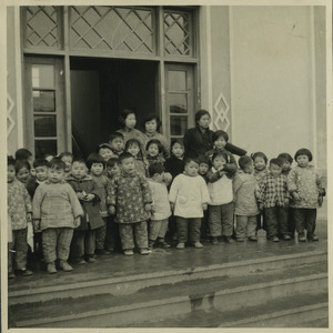 Children and teachers standing on stairs