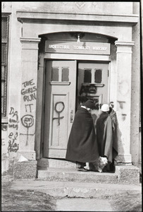 Women's occupation of the Architectural Technology Workshop, Harvard University: two women in blankets, dog, huddled in doorway to ATW