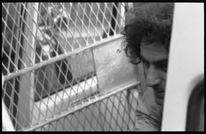 Abbie Hoffman in a police van, getting arrested for wearing an American flag shirt