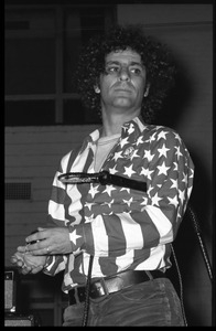 Abbie Hoffman in his American flag shirt, with yo yo in hand and whip under his arm