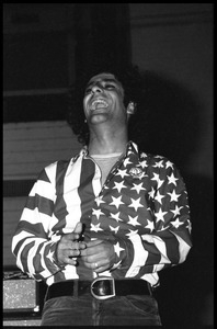 Abbie Hoffman in his American flag shirt, head cocked back, laughing