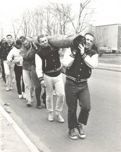 Students carrying a telephone pole during Work Week, 1969