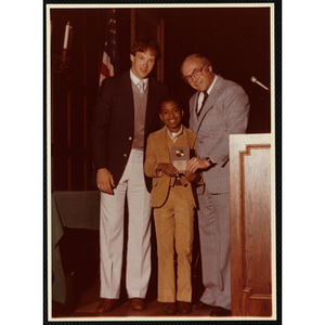 Bernard White receives an award from Robert Cleary, Overseer of the Boys' Clubs of Boston, at right, and an unidentified man