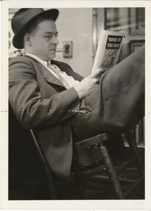 Photograph of Don Sullivan leaning back in a chair, reading
