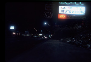 Back-lit motel sign at night: 'color TV heated pool No'