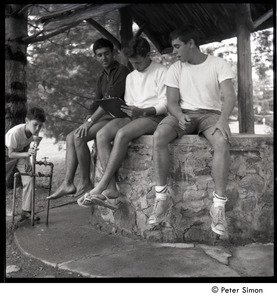 Camp Arcadia: three campers seated on a well