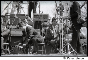 Resistance on the Boston Common: Staughton Lynd seated on the dais, reaching into a bag, Howard Zinn to his left clapping