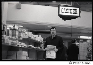 Bill Baird, contraception rights advocate, at a pharmacy, holding up the day's newspaper