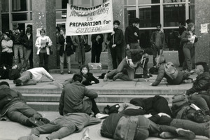 Staged die-in at UMass Amherst, beneath banner reading 'Preparation for nuclear war is preparation for suicide'
