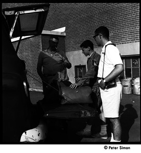 Camp Arcadia: camper and staff removing luggage from the back of a station wagon