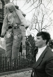 Right wing protester standing by effigy of Abbie Hoffman dressed in Moscow University sweatshirt hanging from tree, Northampton Courthouse