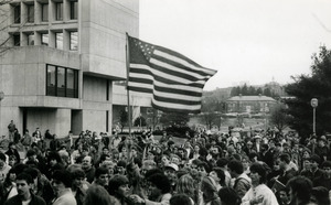 Protesters on UMass Amherst campus, one waving a large American flag