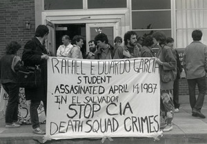 Protesters in front of Student Union at UMass Amherst holding a banner reading 'Rafael Eduardo Garcia student assassinated April 14, 1987 in El Salvador. Stop CIA death squad crimes'