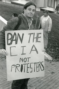 Protester holding a sign reading 'Ban the CIA not protesters': in front of Whitmore Building, UMass Amherst