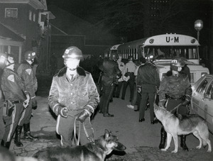 Police in riot gear and dogs, staging near UMass Amherst buses