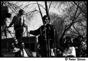 Resistance on the Boston Common: Terry Cannon (draft resister and member of the Oakland 7) addressing the crowd, Howard Zinn seated on stage (far left)