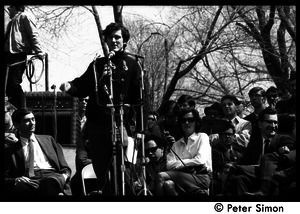 Resistance on the Boston Common: Terry Cannon (draft resister and member of the Oakland 7) addressing the crowd, Howard Zinn (far left) and Noam Chomsky (far right) seated on stage