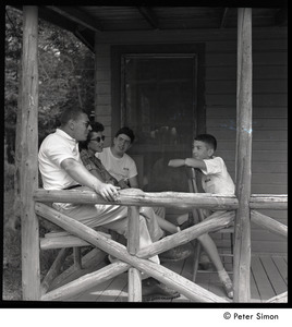Camp Arcadia: camper talking with adults, seated on a cabin porch