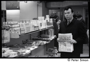 Bill Baird, contraception rights advocate, standing in a pharmacy and holding up the day's newspaper next to pharmacy supplies