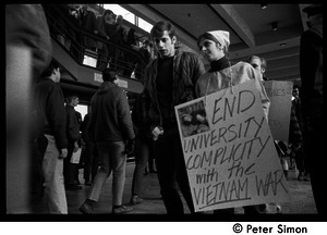 Demonstration against Marine recruiters: protester carrying sign reading 'End university compicity with the Vietnam War'