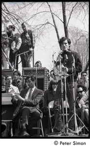 Resistance on the Boston Common: Terry Cannon (draft resister and member of the Oakland 7) addressing the crowd, Howard Zinn checking his notes on stage (far left)
