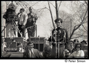 Resistance on the Boston Common: television camera filming as Terry Cannon addresses the crowd, Howard Zinn seated on stage (left)