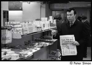 Bill Baird, contraception rights advocate, at a pharmacy, holding up the day's newspaper next to supplies