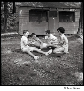 Camp Arcadia: campers seated on a blanket in front of a cabin