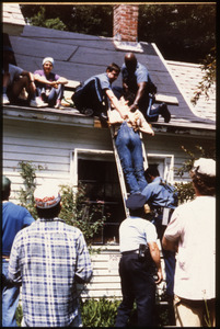 State troopers removing a handcuffed protester from the roof of the home of war tax resisters Randy Kehler and Betsy Corner