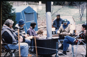 Protesters near the home of war tax resisters Randy Kehler and Betsy Corner, seated outside around a wood stove